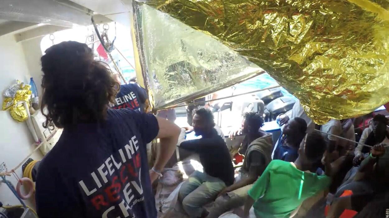 Des passagers rescapés à bord d'un navire d'aide humanitaire.