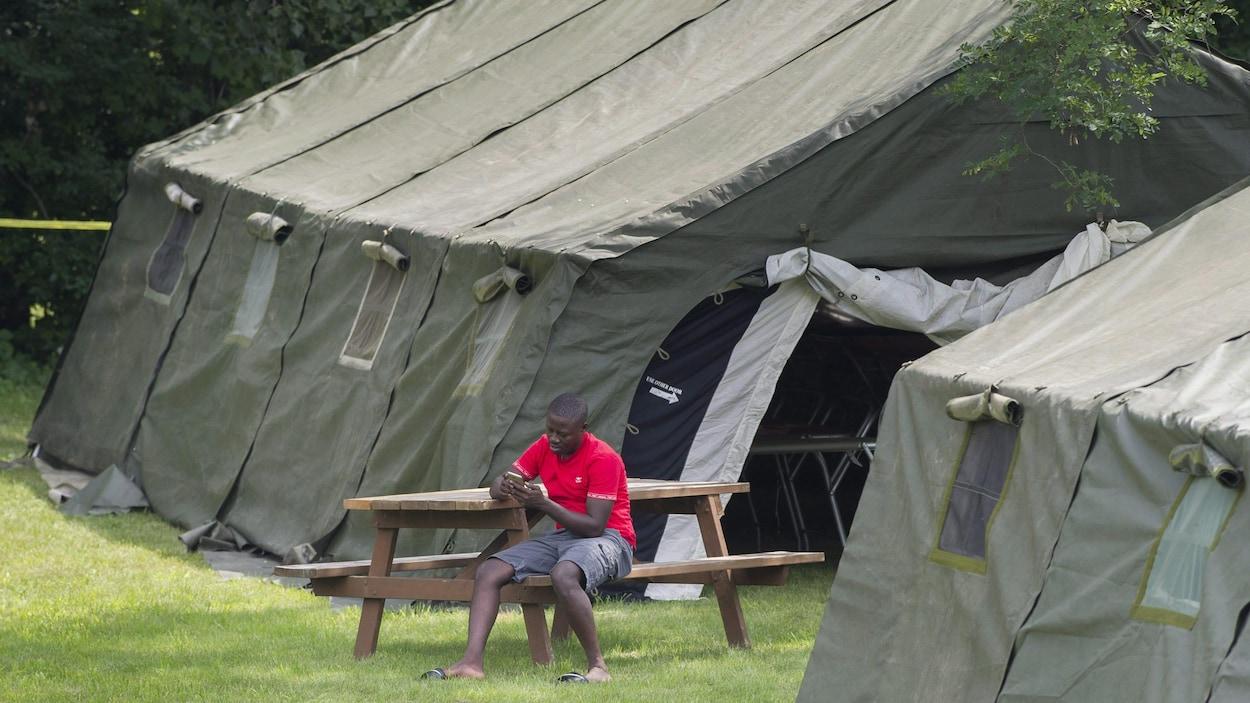 Un homme assis à une table consulte son téléphone, dans un campement.