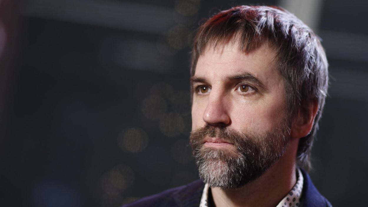 Un homme barbu accorde une entrevue à la caméra.