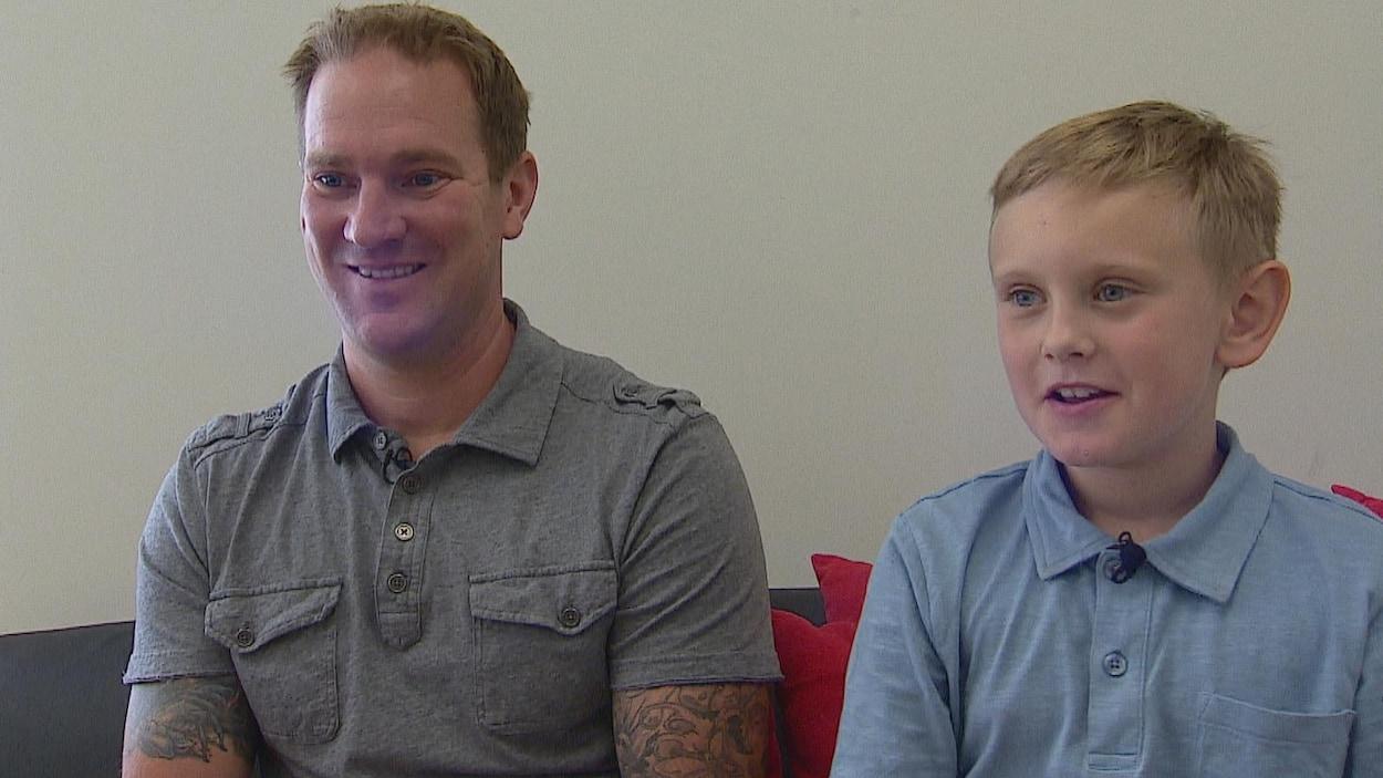 Le père Mike est assis sur un canapé avec son fils Maxwell sont assis sur un canapé. Ils sourient.