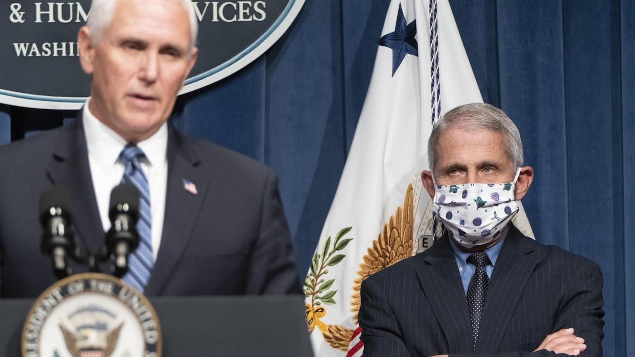 Le directeur de l'Institut national des allergies et des maladies infectieuses, Anthony Fauci, portant un masque, regarde le vice-président Mike Pence.