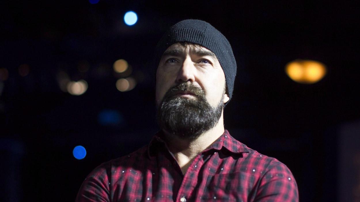 Le musicien Mike Taylor portant une tuque et une chemise carreautée.