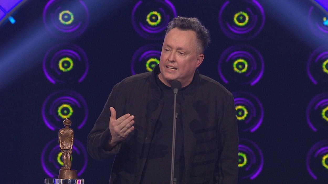 L'homme est debout sur la scène et parle dans un micro.
