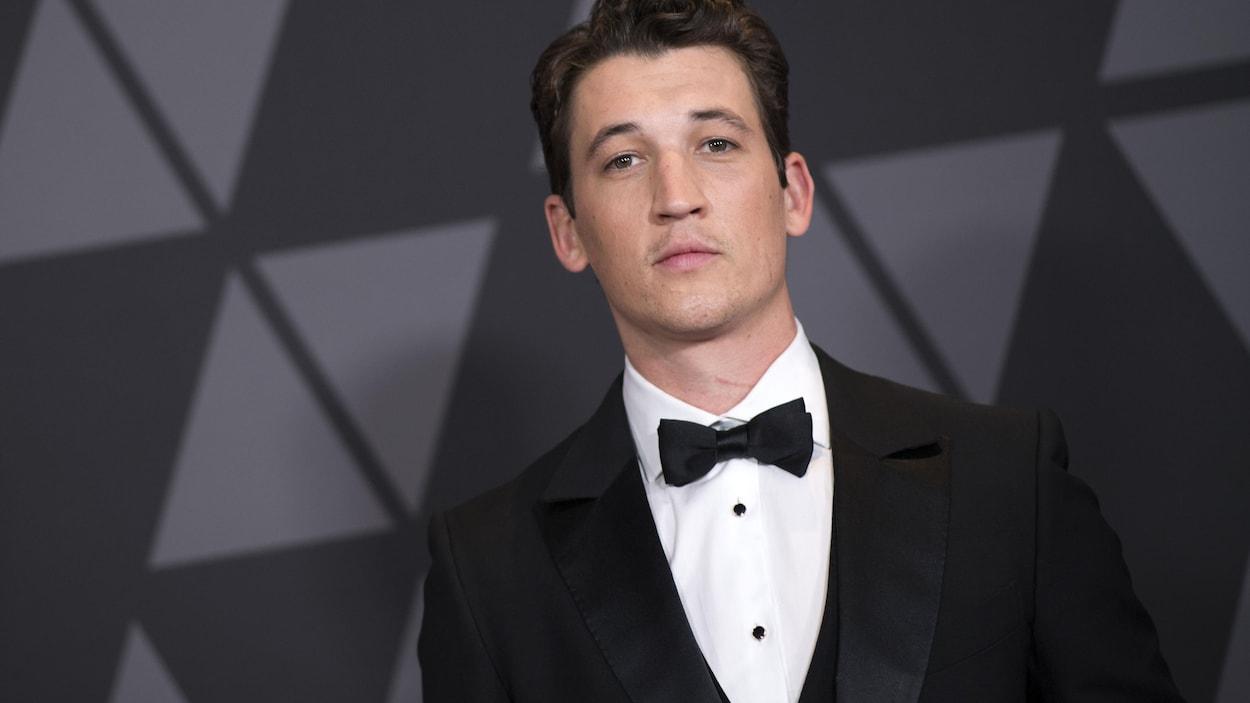 L'acteur vêtu d'un costume noir avec un noeud papillon pose pour les photographes.