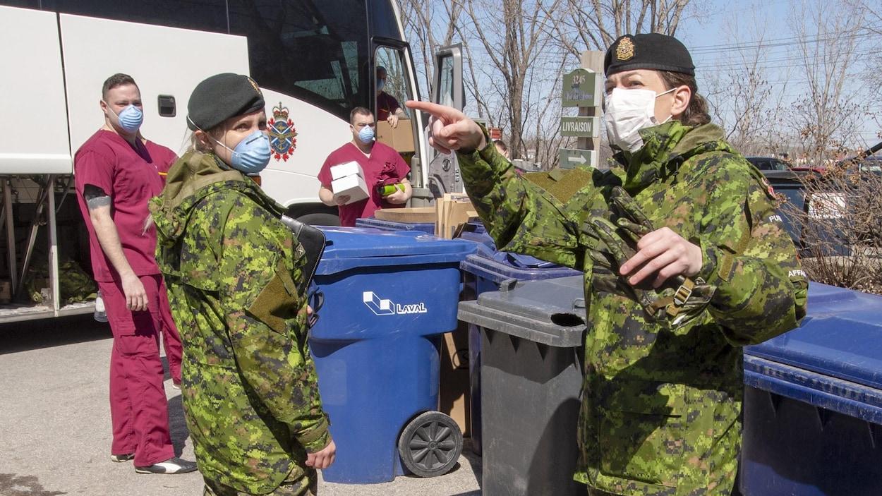 Plan large de militaires portant des masques devant des bacs de recyclage.