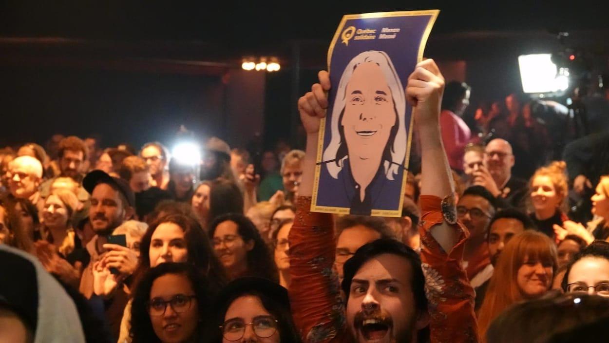 Dans la foule, un militant tient une affiche de Manon Massé.