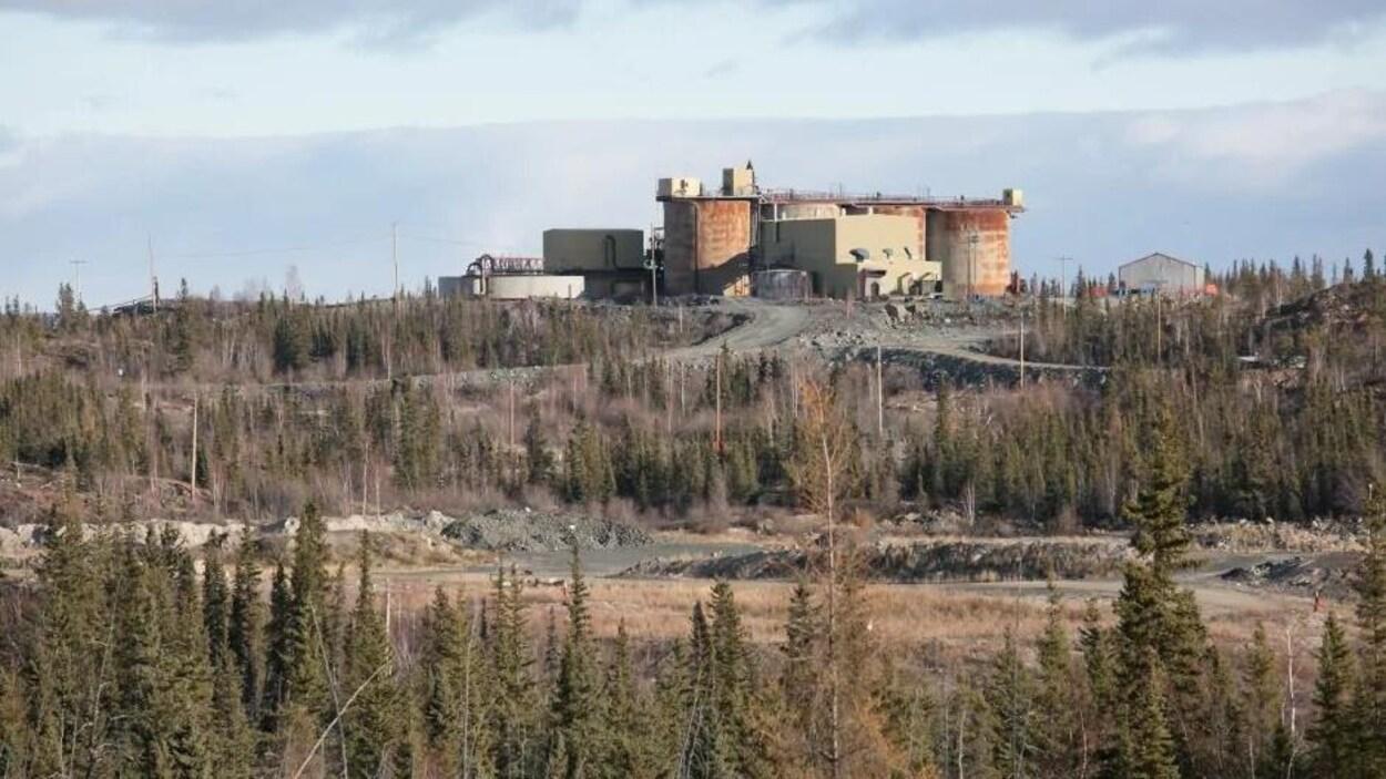 Une mine abandonnée entourée d'un boisé.