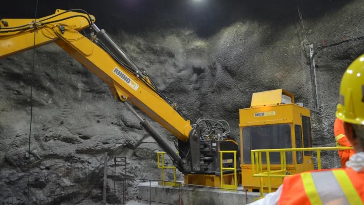Un travailleur de dos regarde une paroi dans une galerie souterraine avec une pièce d'équipement.