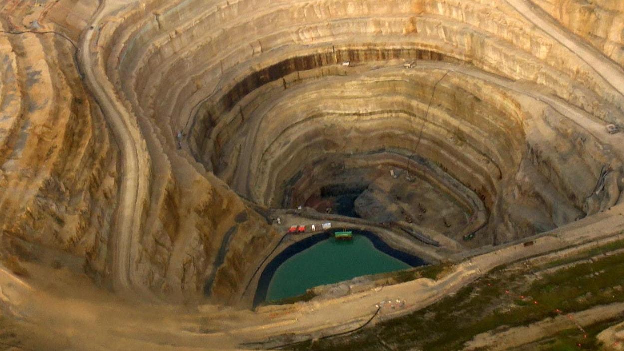 Vue aérienne d'un puits de mine à ciel ouvert. On aperçoit un bassin d'eau et des véhicules miniers.