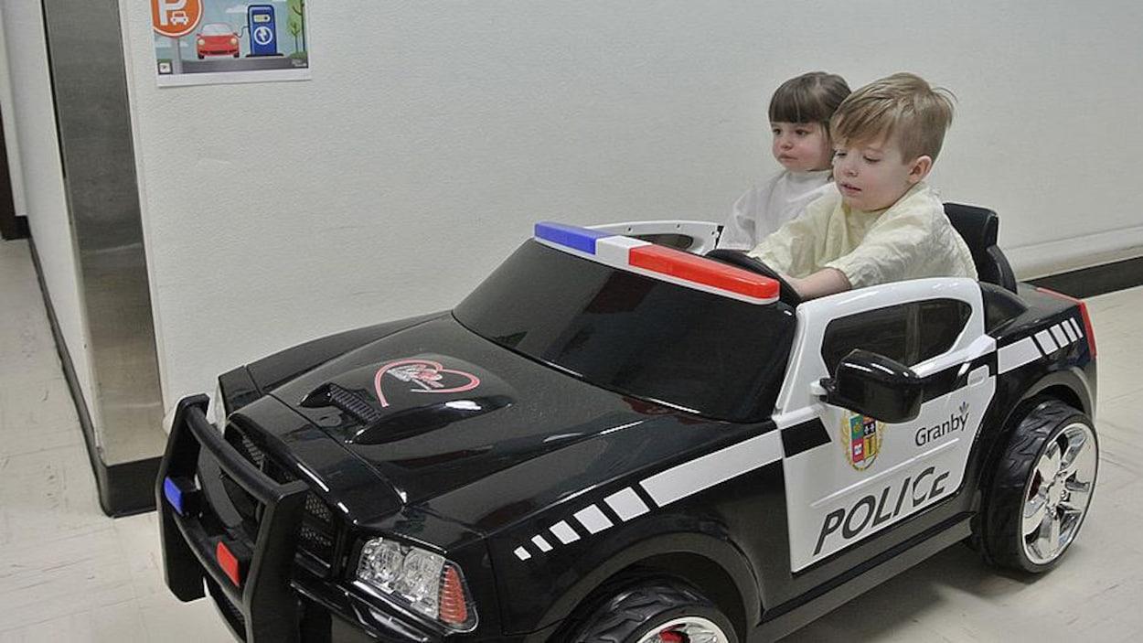 Deux enfants au volant d'une mini voiture aux couleurs du Service de police de Granby.
