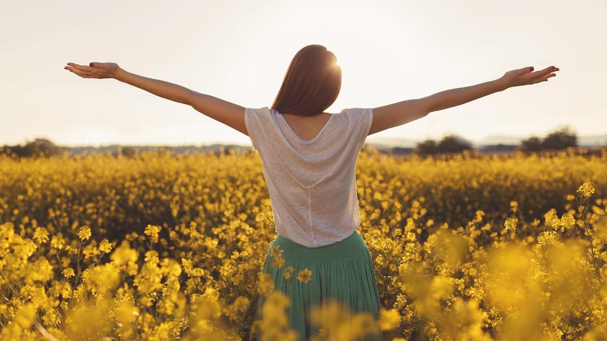 Femme profitant du soleil dans un champ de fleurs jaunes