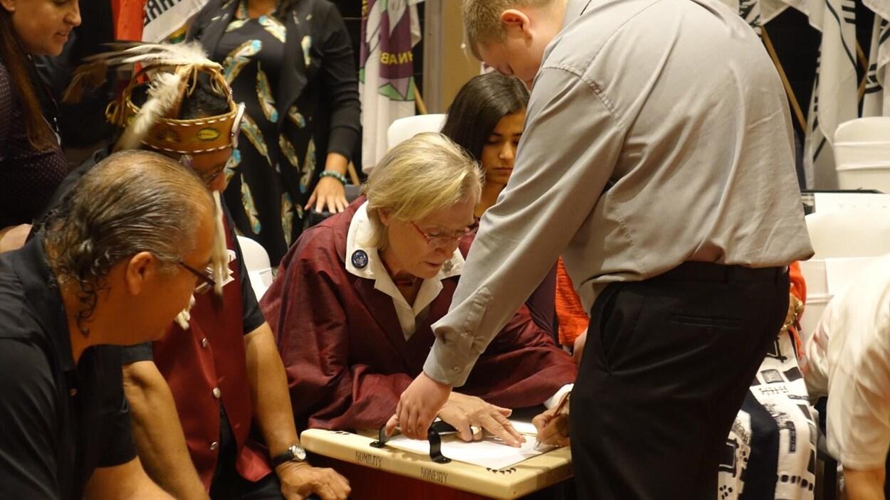 La ministre Carolyn Bennett en train d'apposer sa signature.
