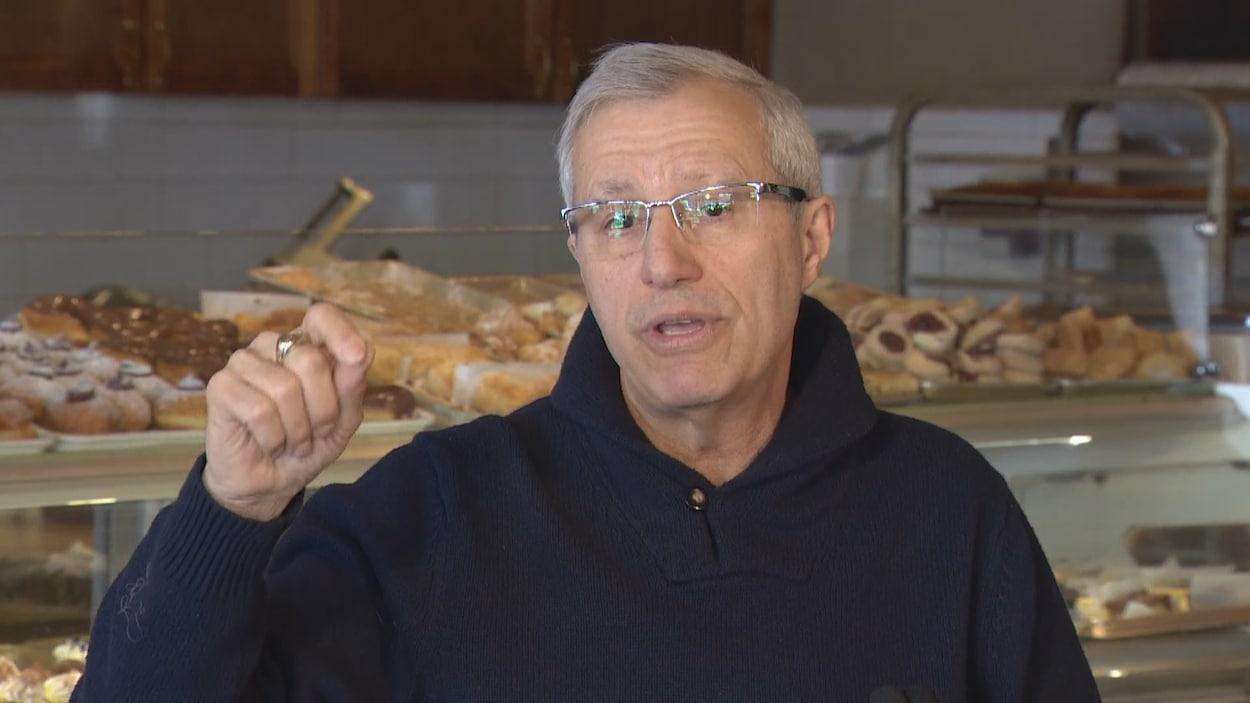 Photo d'un homme portant un chandail noir et des lunettes, la main dans les airs