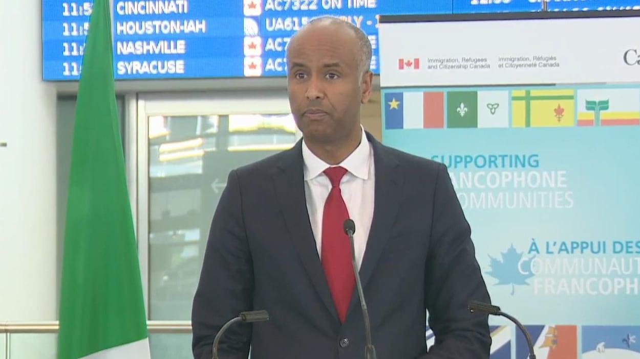 Ahmed Hussen portant un complet devant un micro.