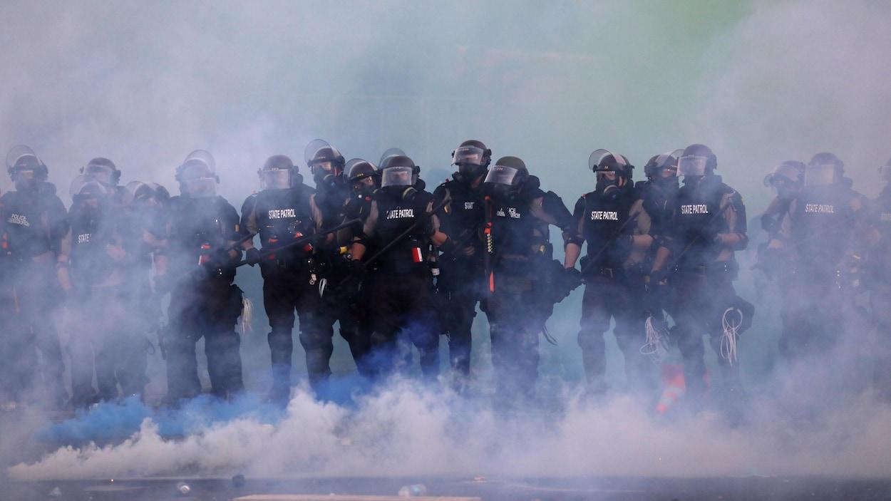 Plusieurs policiers en équipement de protection à travers la fumée de gaz lacrymogène.