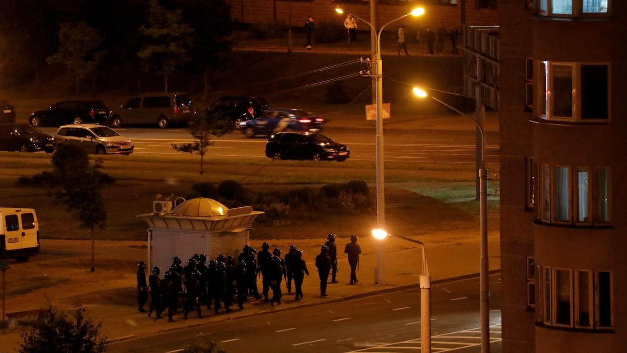 Des membres des forces de sécurité marchent en groupe sur un trottoir alors que la rue semble calme et les lampadaires allumés.
