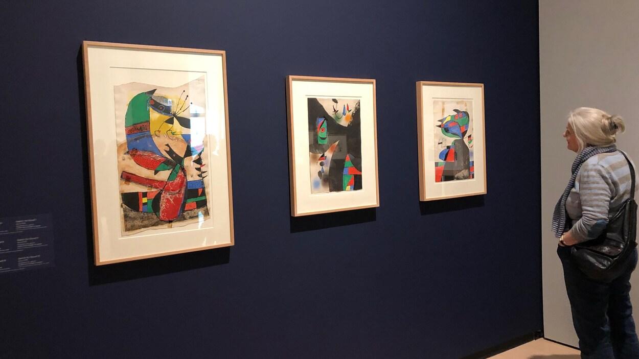 Une visiteuse de l'exposition devant trois oeuvres, des toiles, affichées sur un mur de couleur bleue.