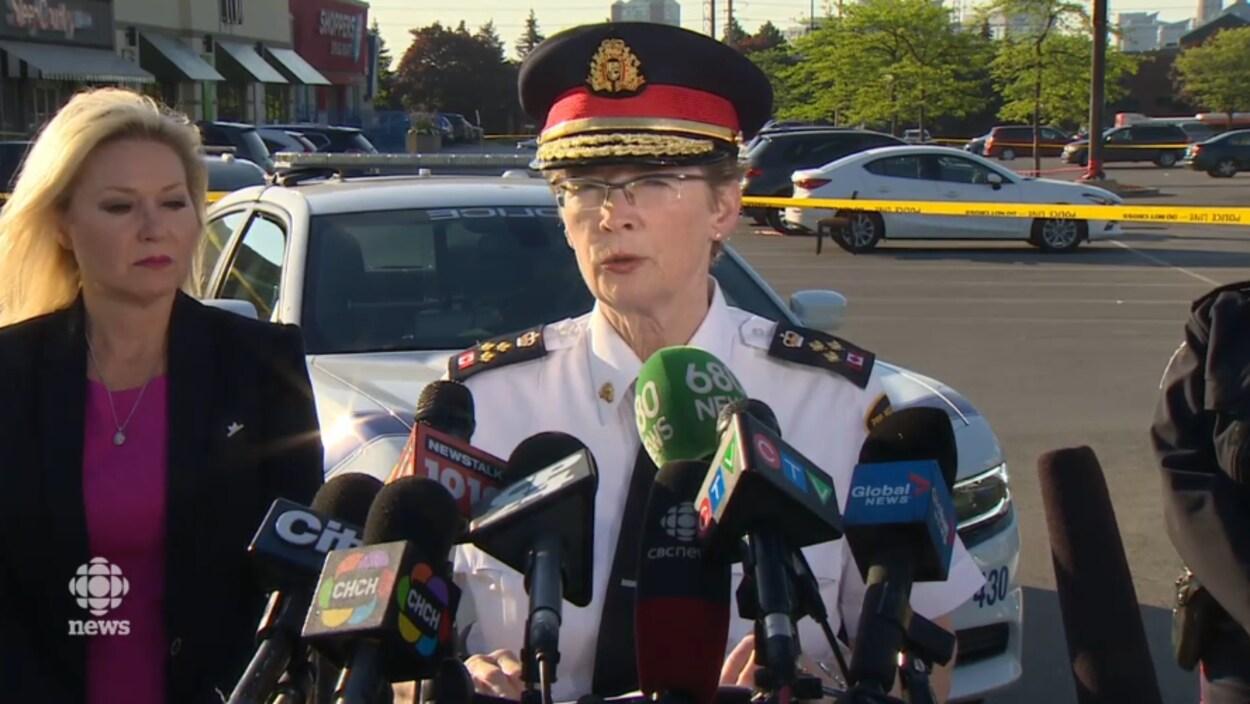 Une femme portant une casquette et un uniforme de police devant des microphones