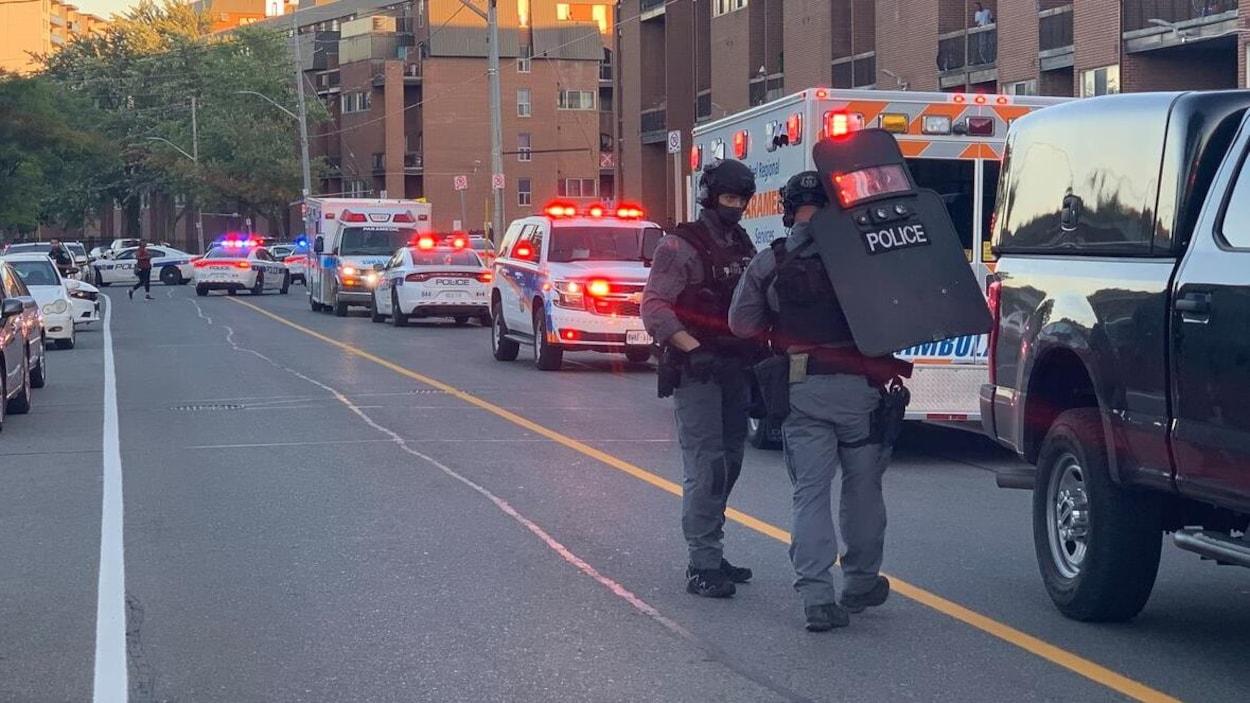 Des policiers lourdement équipés dans une rue remplie de voitures de police et d'ambulances.