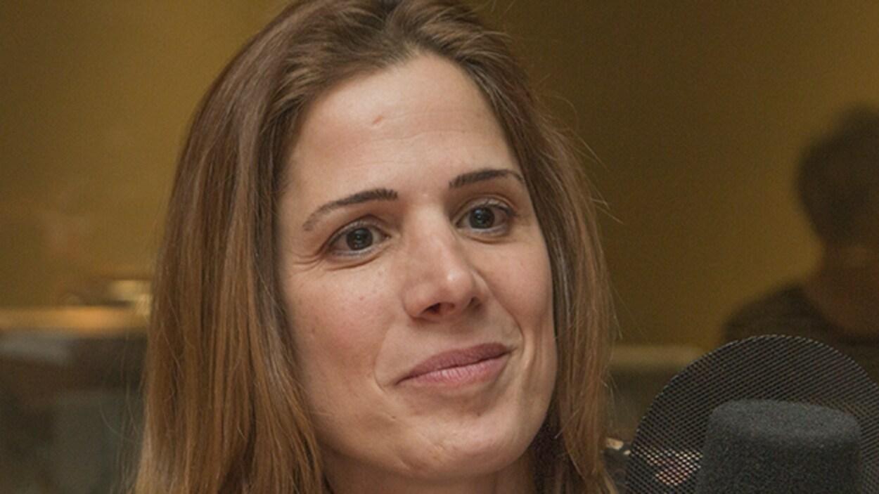 Pascale Déry lors d'une entrevue radiophonique sourit, près du micro.