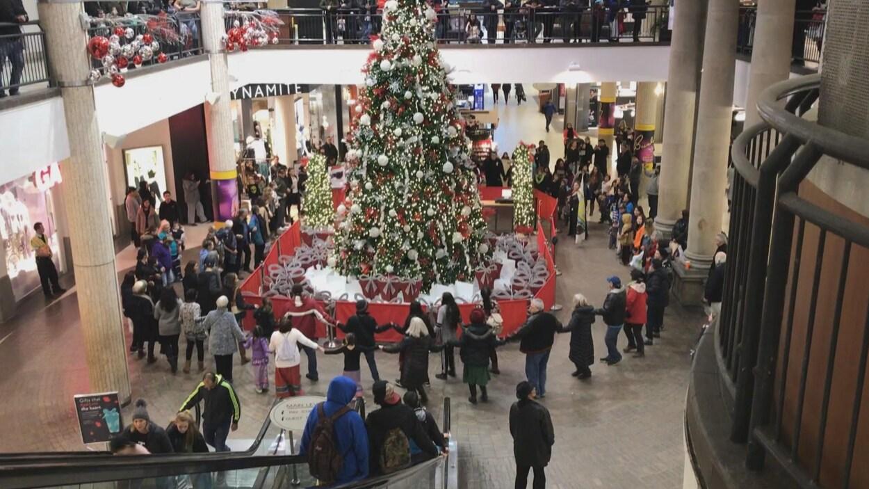 Des gens dansent autour d'un sapin de Noël au milieu d'un centre commercial.