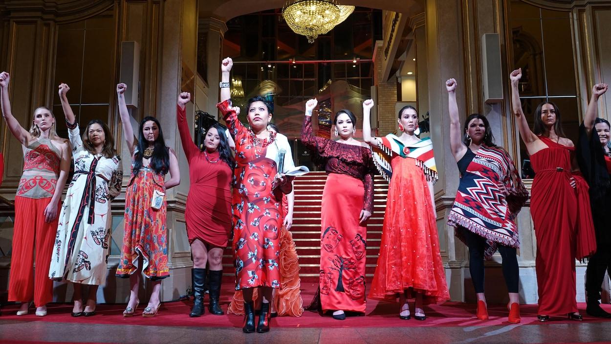 Une dizaines de femmes portent des vêtements qui arborent la couleur rouge et lèvent le poing droit.