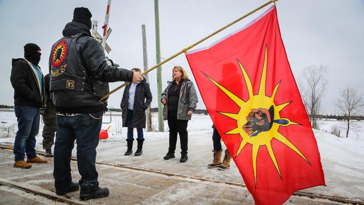 Des manifestants tiennent un drapeau mohawk.