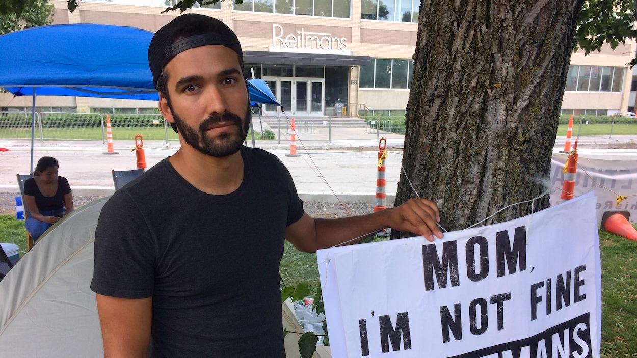 L'influenceur Kubben Quiñonez tient une pancarte où il est écrit « Mom I'm not fine because of Reitmans »
