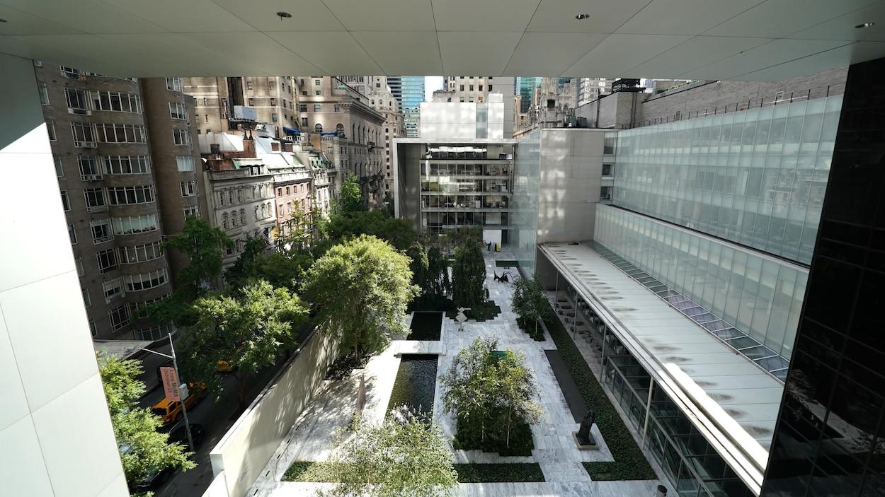 Une galerie extérieure du musée est visible à partir d'un étage supérieur du MoMA, à New York. On aperçoit également des bâtiments de la ville autour.