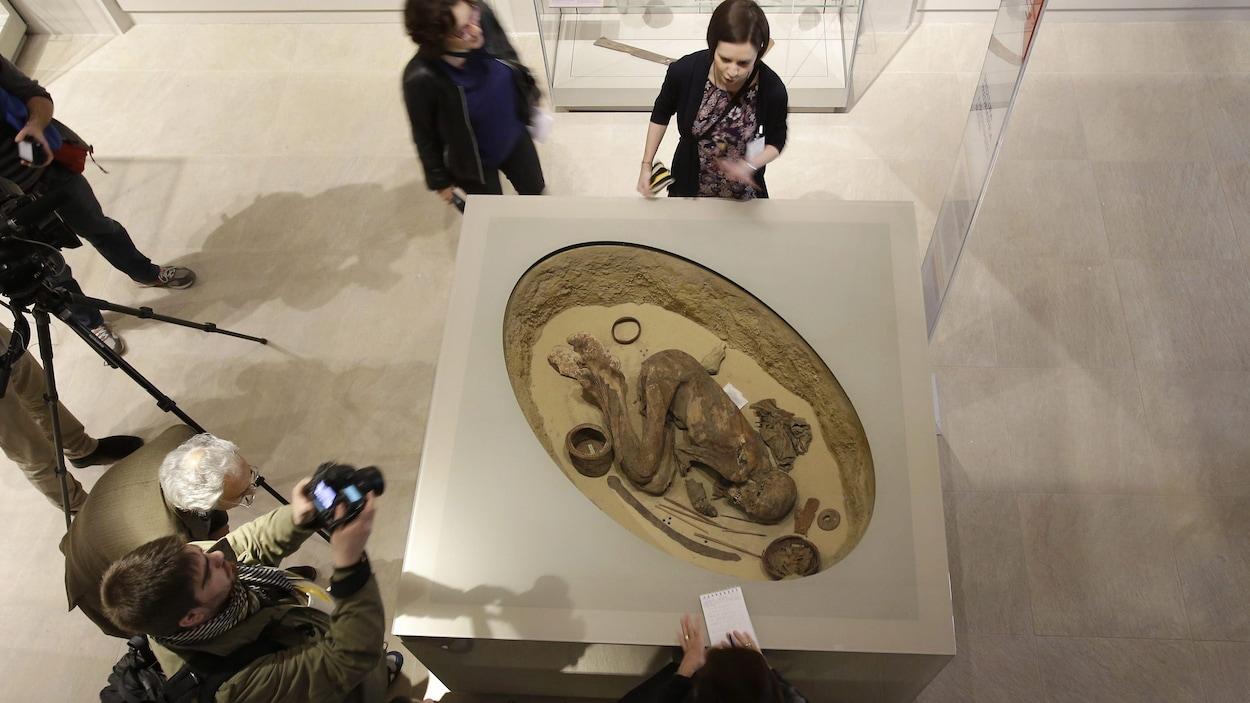 Des visiteurs observent la momie en position foetale.