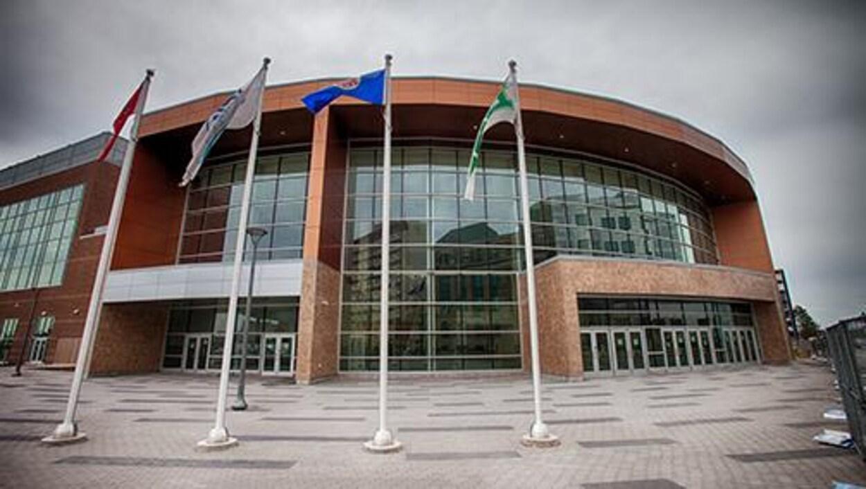 Quatre drapeaux flottent devant l'entrée du bâtiment
