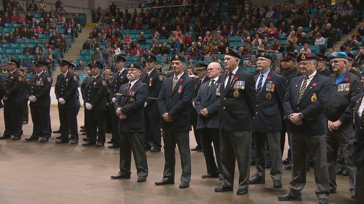 Un groupe d'anciens combattants au garde-à-vous au milieu du Colisée de Moncton. La foule occupe presque tous les gradins.