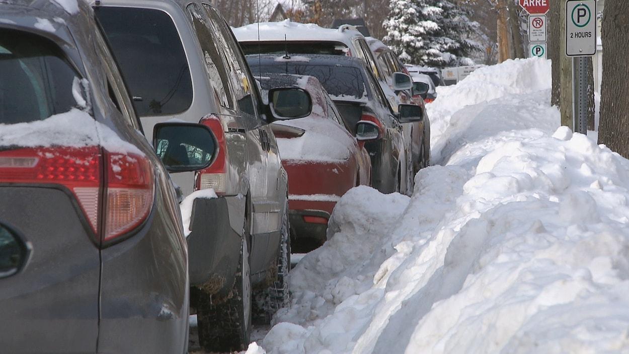 Des voitures garées le long d'une rue enneigée.