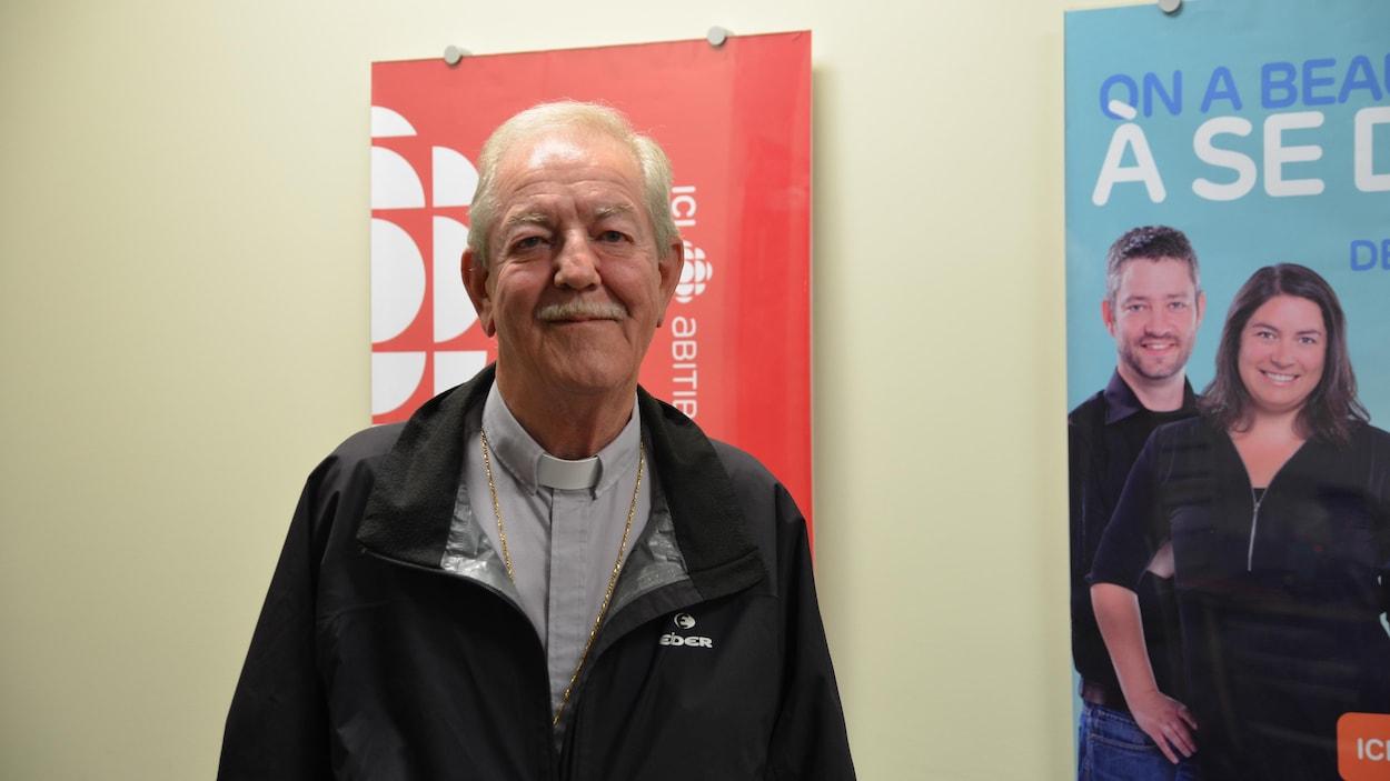 Monseigneur Dorylas Moreau devant l'affiche de Radio-Canada en Abitibi-Témiscamingue.