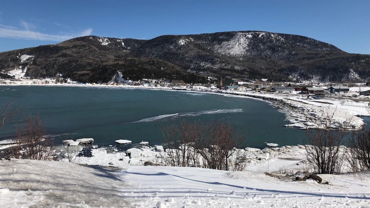 Municipalité au pied de montagnes située dans une baie.