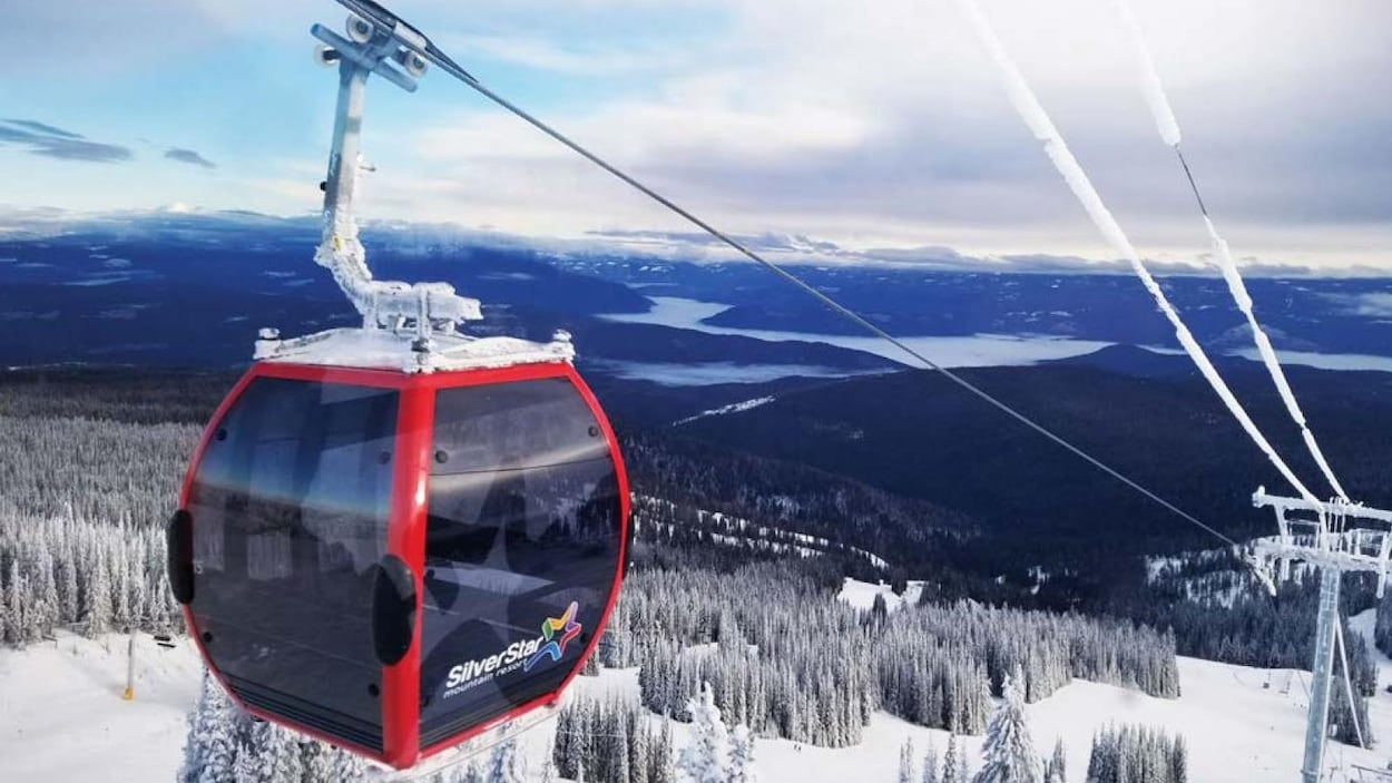 Une gondole, l'hiver, on a une vue sur des montagnes, de la neige et des nuages.