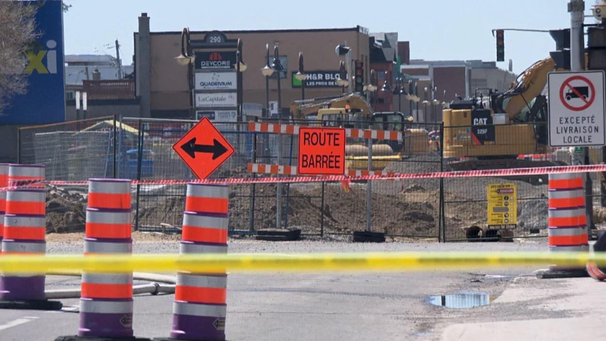 L'intersection est bloquée par des clôtures et des cônes de construction.