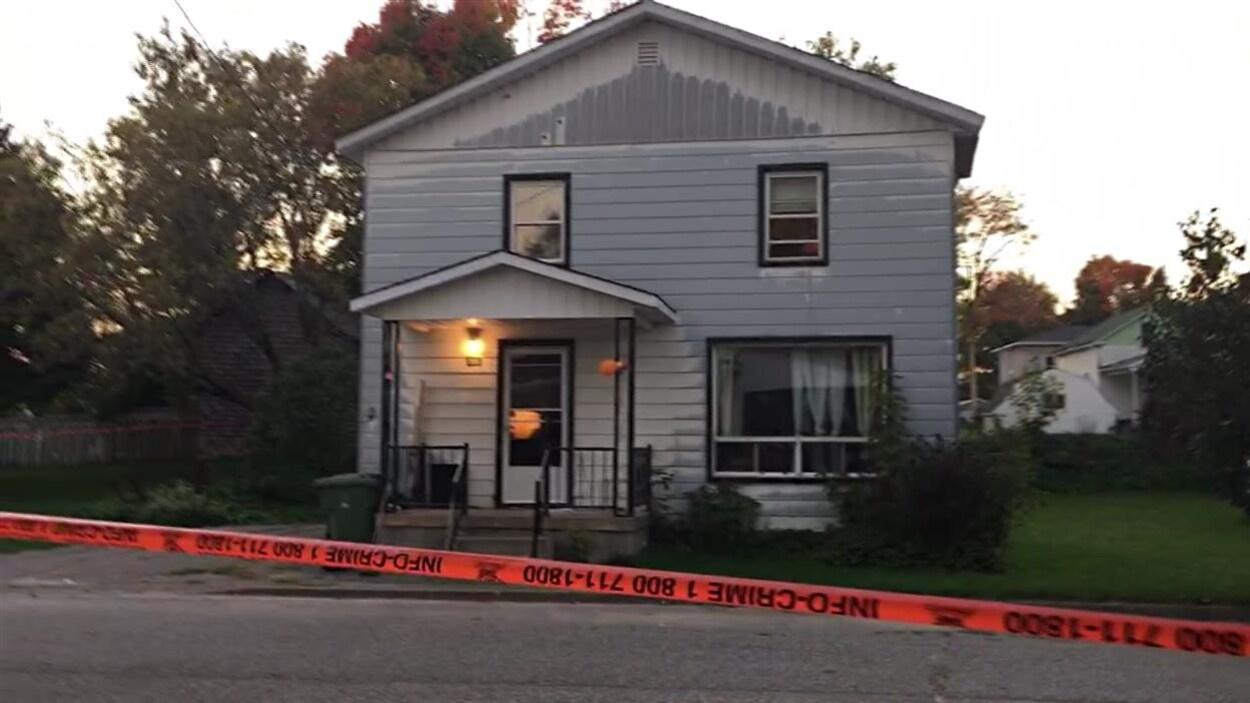 Une maison est entourée d'un ruban de sécurité de la police.