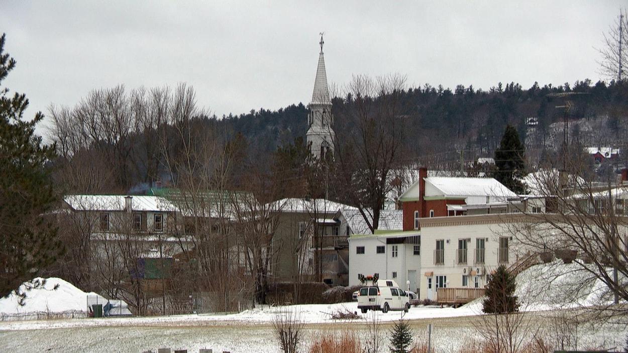 Le village de Montebello en hiver. À travers les maisons, le pignon de l'église est visible.
