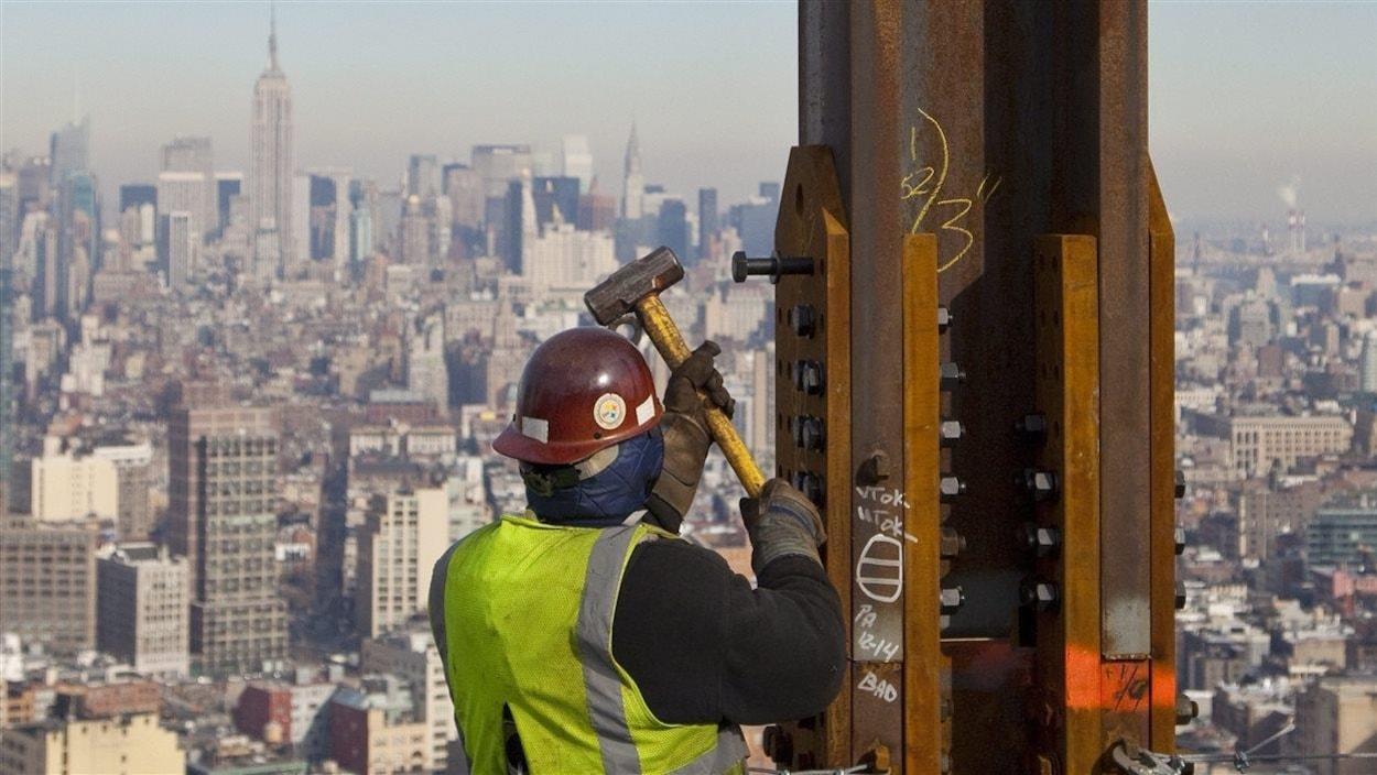 Le 16 décembre 2010, un charpentier de l'acier assemble des poutres au One World Trade Center à New York. En arrière-plan: l'Empire State Building.