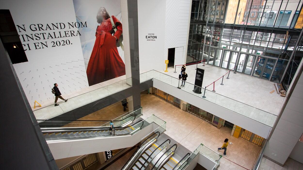 Une femme seule descend un escalier roulant.