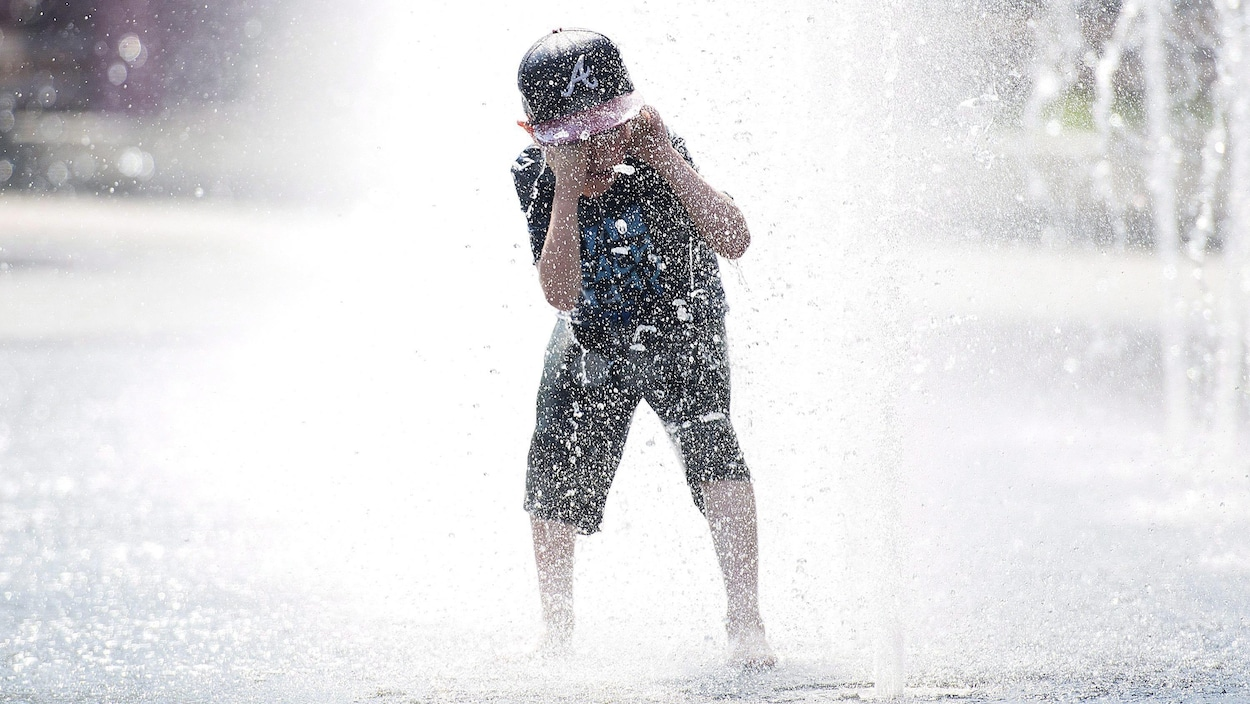 Un enfant s'amuse dans une fontaine.