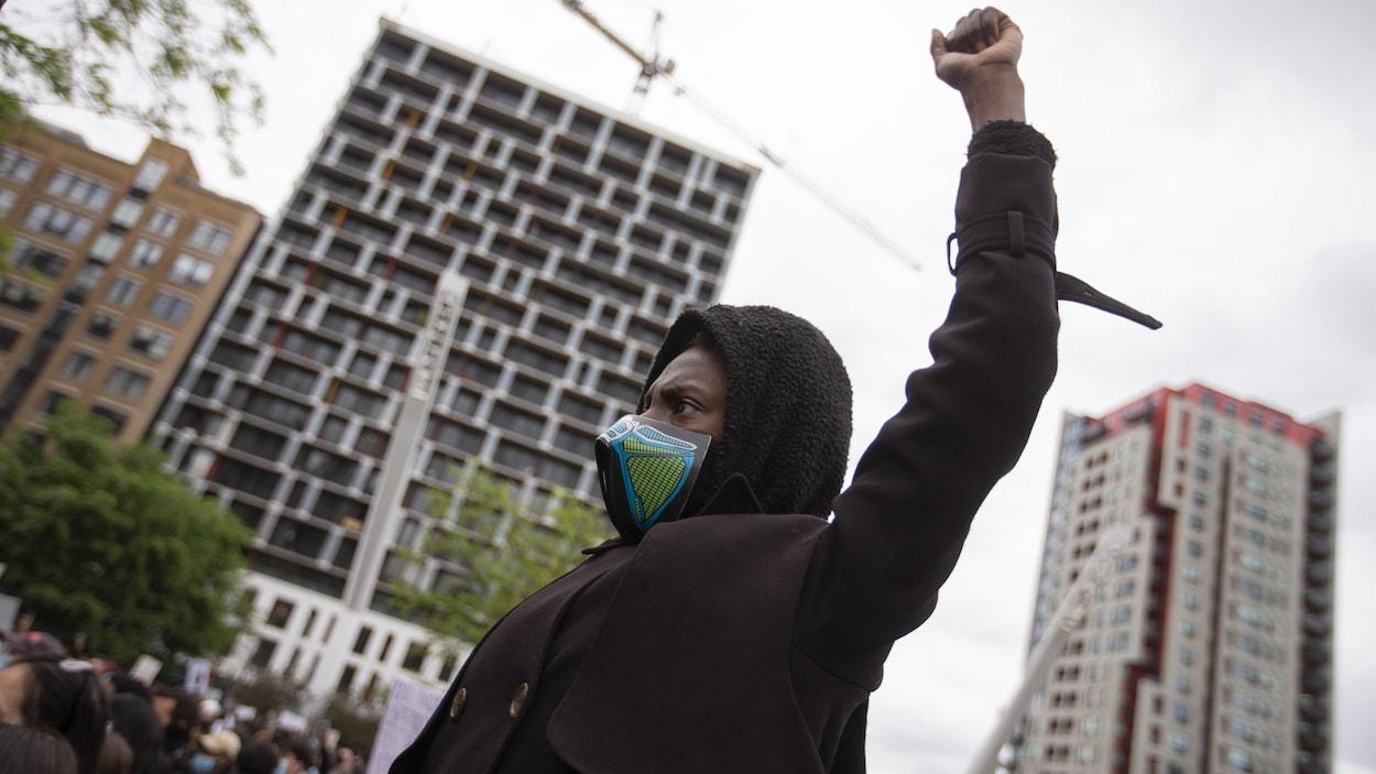 Un manifestant portant un masque et avec le poing gauche en l'air.
