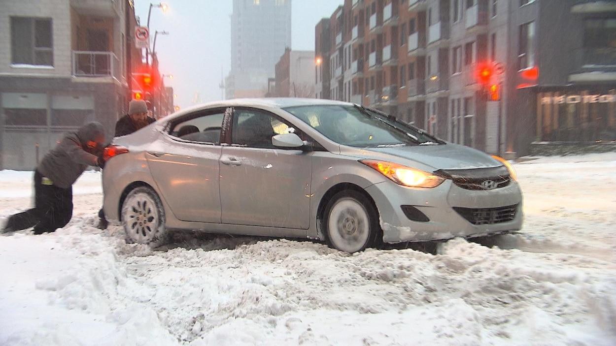 Trois hommes, un au volant et deux autres dehors, poussent un véhicule enlisé dans la neige.