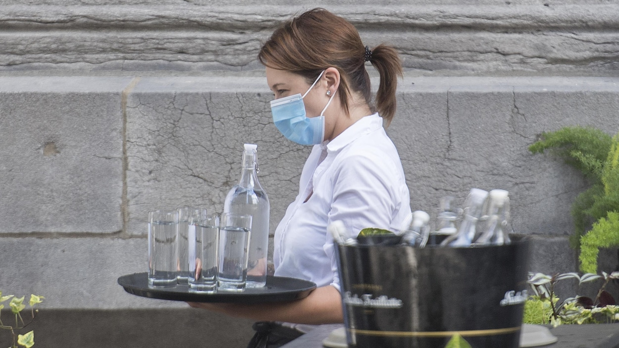 Une serveuse qui travaille sur une terrasse porte un masque.