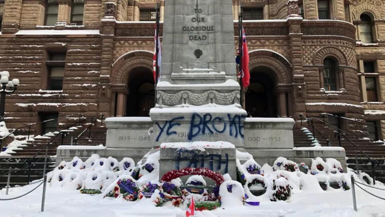 """Le monument commémoratif devant l'ancien hôtel de ville de Toronto entouré de gerbes de fleurs sous la neige, sur lequel quelqu'un a écrit avec une bombe de peinture : """"Ye broke faith""""."""