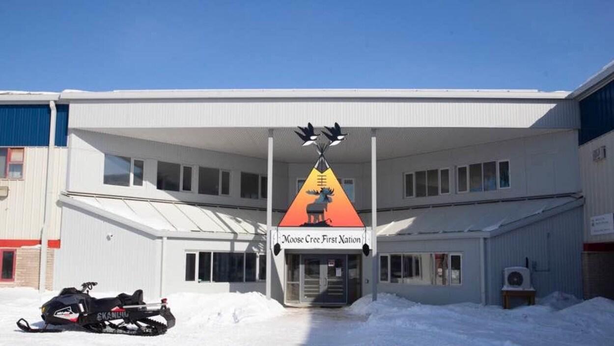 Une motoneige à l'extérieur de l'édifice de la Première Nation Moose Cree.