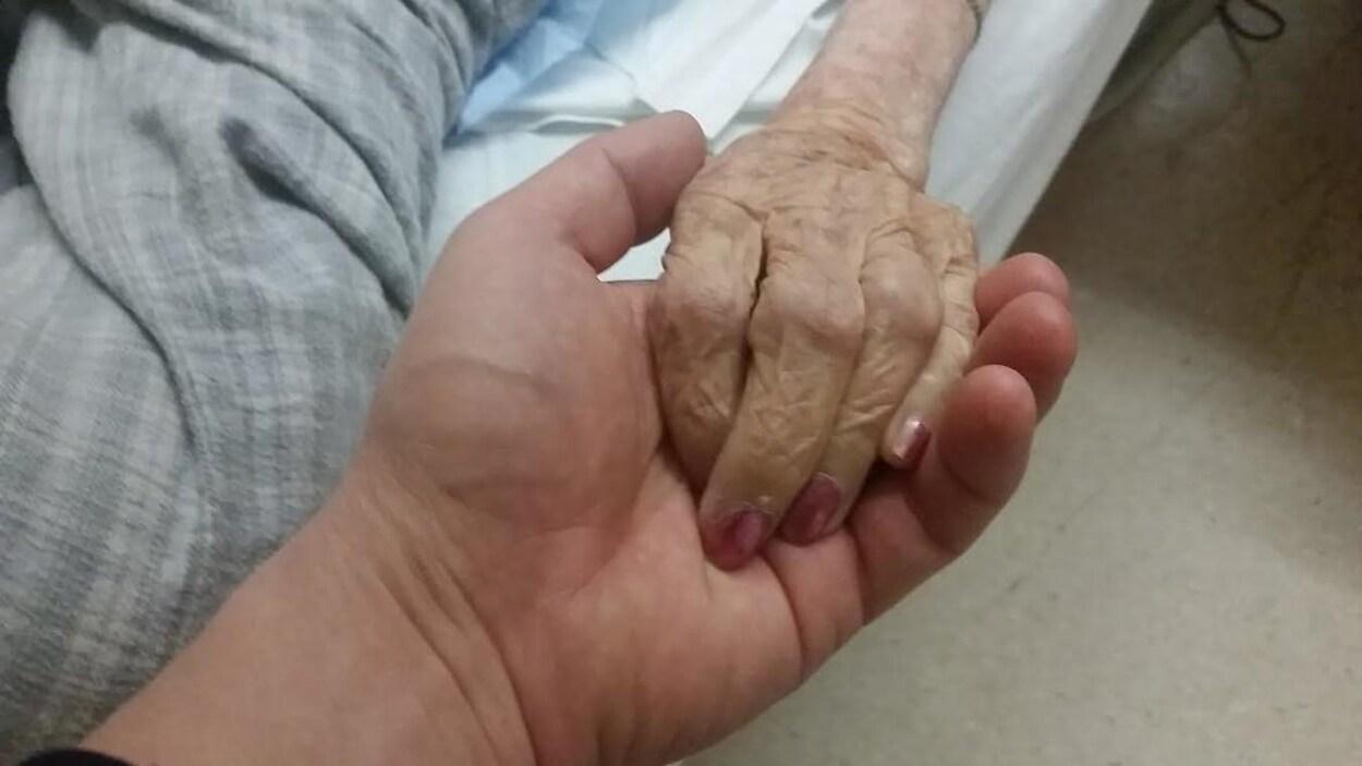 La main d'une femme en fin de vie, allongée sur un lit médical, repose dans la main d'une personne qui semble être en bonne santé. La main de la personne en fin de vie est maigre et ridée, avec les jointures apparentes. Les ongles sont vernis et manucurés.