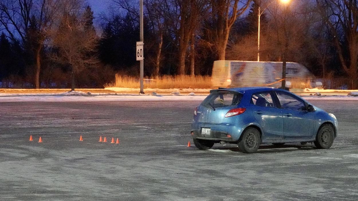 Une petite voiture seule au milieu d'un stationnement.