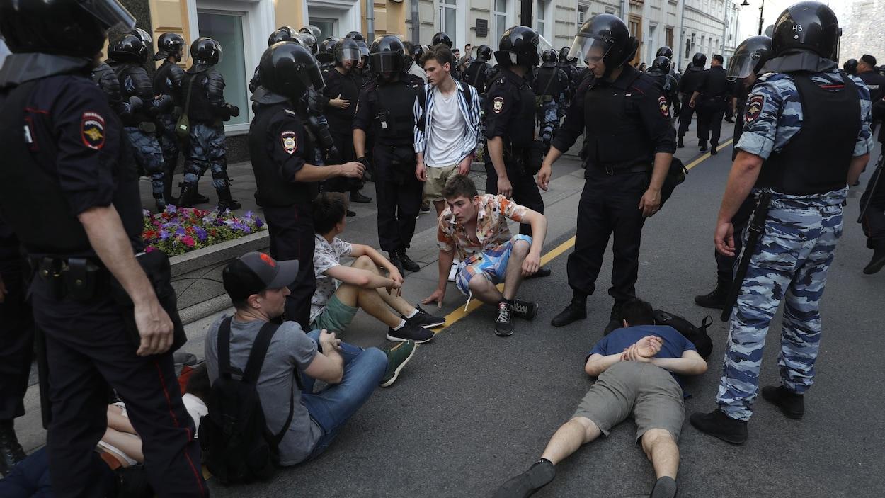 Des manifestants sont allongés par terre, des policiers les encerclent.